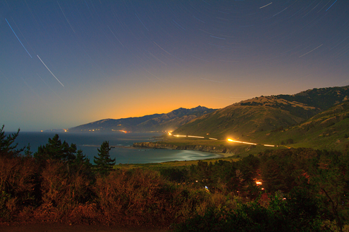 A 45-minute long record of the light in Big Sur. The headlights on Highway 1 wrap around the edge of the Central Coast from the campfires of the Plaskett Creek Campground (foreground) extending to the Pt. Sur Lighthouse (last light on the left). Stars streak in arcs around Polaris with the orange city lights of the Monterey Peninsula glowing over the Santa Lucia Mountains.