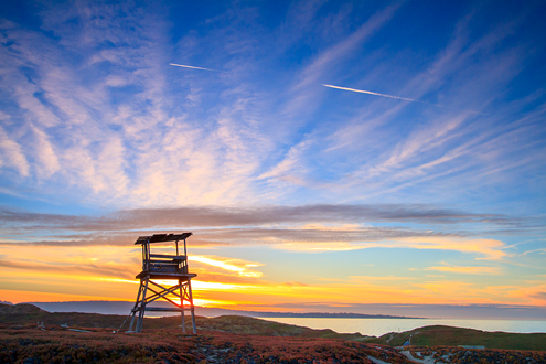 A World War II army watch tower overlooks the sand dunes and Monterey Bay at sunset with the Monterey Peninsula in the background.