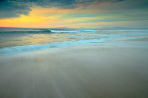 A painterly looking beach sunset in pastel colors over the Monterey Bay with Santa Cruz on the horizon.