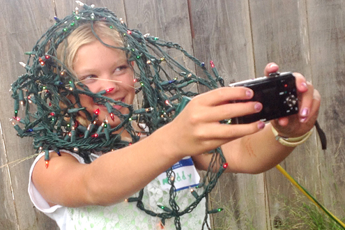 Young girl wrapped in Christmas lights and taking a self-portrait.