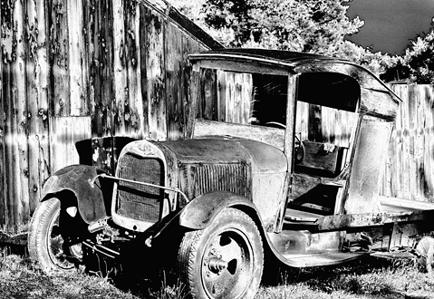 Dilapidated truck next to a wooden barn
