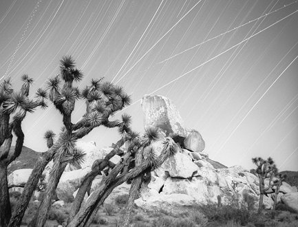 Lately I've taken to creating compositions that juxtapose eternal motion with the seemingly inanimate. This shot depicts 5 hours of the earth's rotation spinning us past our universe, a host of military aircraft coming and going from the 29 Palms Marine Airbase, localized gusts of wind blowing some trees but not others, and climbers descending Head Stone Rock (the white squiggles are their headlamps)—all by 4 hours of setting moonlight and 1 hour of darkness.