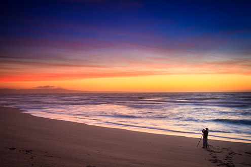 Lone photographer shooting the sunset at ocean's edge