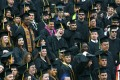 A wall of graduates in black gowns and hats, and 1 with headphones rocking out to music.