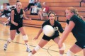 3 women volleyball players return the ball.