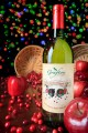 Wine Bottle surrounded by spilt apples and cranberries with colorful background lights.