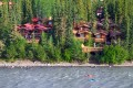 Cabins nestled in a forest along a river with kayakers paddling by.