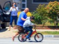 Father teaches his son to ride a bike.