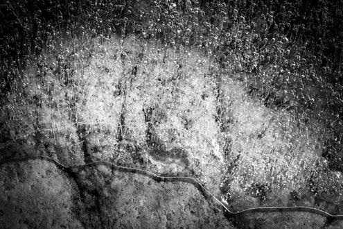 Abstract science fiction-like black and white image of a bubbling liquid oozing over a rock.