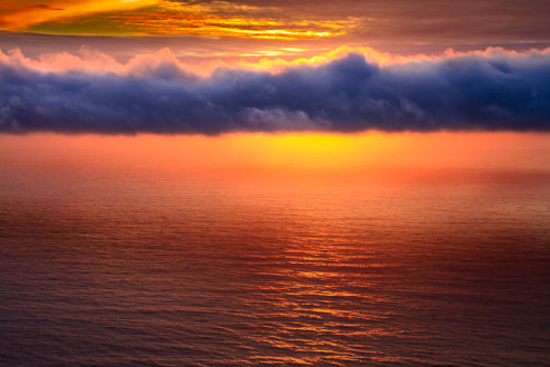 A blue shadowy cloud column obscures the sun just before sunset lighting the sky and ocean a fiery orange.
