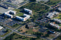 State college campus from the air that includes its visitors center and several dormitory buildings.