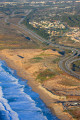 Coastal freeway wraps around a Monterey Bay beach.