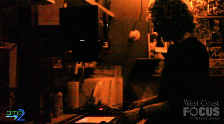 Zach Weston making a print in a darkroom.