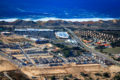 Aerial photo of half-completed development project including a theater, big box shopping center, commercial offices, medical facilities, single and multi family housing, hotel, and restaurants with the Fort Ord Dunes State Park and Monterey Bay in the background.