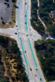 Aerial photo of traffic on a road with distinctly green painted bike lanes.