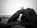 Ghostly figures standing atop a rock arch with misty ocean around them.