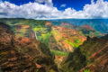 Red canyons walls dressed with bright green foliage with a long white waterfall and river, blue sky, and fluffy clouds.