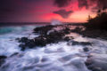 The tide draining over lava rocks towards another incoming wave crashing with a red sunset sky.