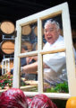 Chef Todd goofing off in front of a rustic window stage prop.
