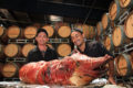 2 Chefs display a roast pig with a wall of wine barrels in the background.