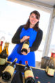 A winemaker poses with her bottles.