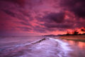 Purple, magenta, red and orange sunset reflected in the pacific ocean with high tide pouring over rocks.