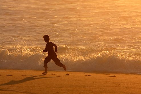 Fort Ord Dunes Workshop Participant example of boy running down the beach at sunset