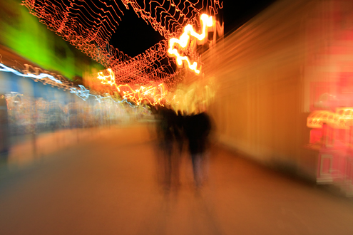 Silhouettes of holiday visitors to Fisherman's Wharf are drawn into the carnival of lights.
