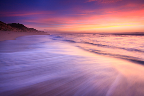 Colorfully lit surf rushes up the beach at twilight with a colorful sky over Monterey and silhouetted sand dunes.