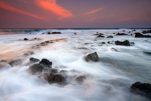 Waves crash with wispy silkiness on ancient lava rocks backed by a setting sun over the Pacific Ocean.