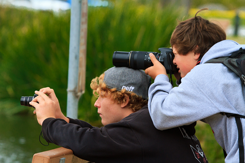 Two young boys, one with his camera on the head of the other.