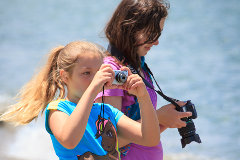 Two young girls at the beach photographing.