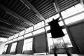 A cloaked figure hovers in the air in front of a wall of warehouse windows and doors.