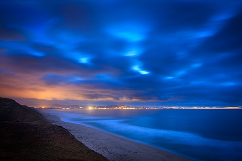 The lights of the Monterey Peninsula bring warmth to a passing storm at sunset.