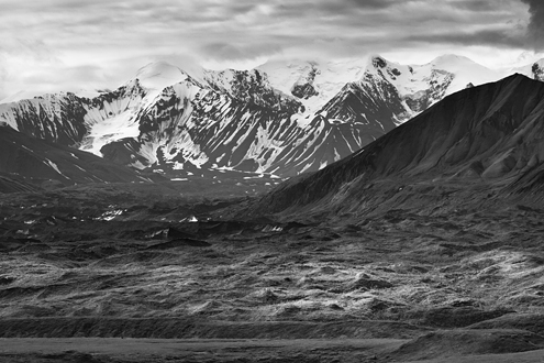 Much of Denali's light is diffused by varying depths of cloud cover, and occasionally some direct sunlight illuminates a spot of land then passes on.