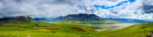 Panoramic photo os expansive landcsape of tundra glacial rivers, mountains, and storm clouds.