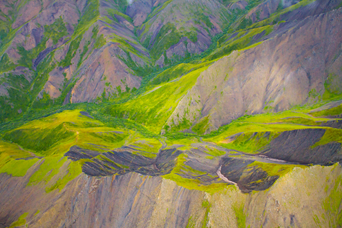 Abstract aerial photo of green and purple mountains.