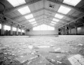 Shattered glass fills the floor of an large aquatic building.