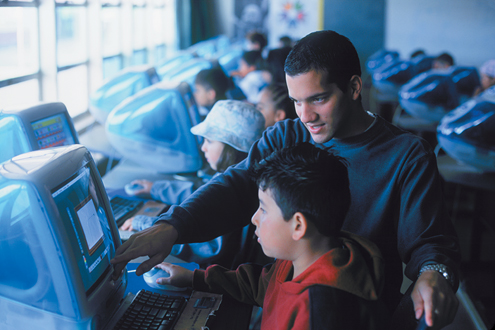 A student teacher assists with a computer class at a Salinas elementary school. This photo was used in Cal State Monterey Bay's student recruitment and fundraising materials.