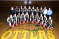 Women's basketball team group photo with otter logo painted on the floor