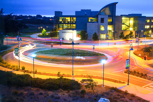 Long exposure of car lights going around a roundabout with a library in the background.