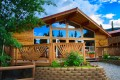 Exterior photo of rustic mountain restaurant with deck and garden.