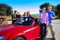 3 couples kiss around a red convertible sports car in front of a vineyard.