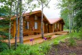 Exterior of log cabin surrounded by trees and garden.