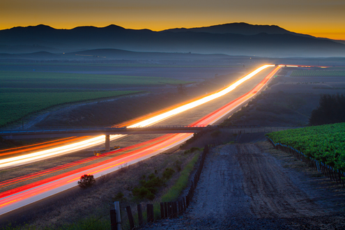 Long exposure of car lights trace the path of a highway through a vineyard landscape at dusk.