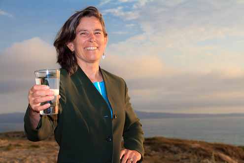 MCWD Director jan Shriner poses with a glass of water with sand dunes, Monterey Bay and Monterey Peninsula in the background.