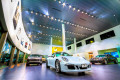 Various Porsche models adown a showroom floor in a big wide angle photo with lots of lights.
