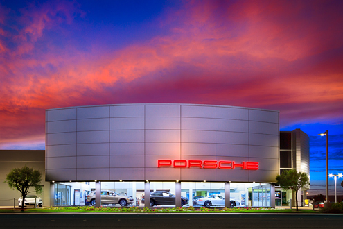 Monterey Porsche Dealership from the street lit up with a dramatic sunset in the background.