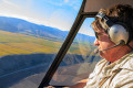 Helicopter pilot flys over vineyards.