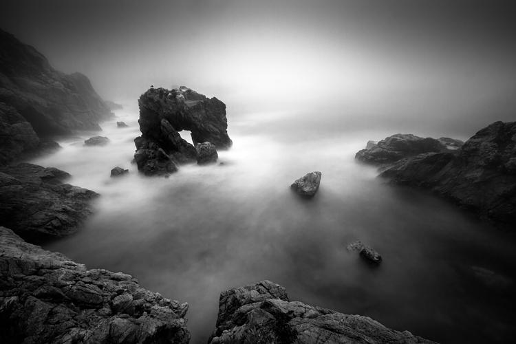 Sun glows behind fog in a dark cove along the California coast.